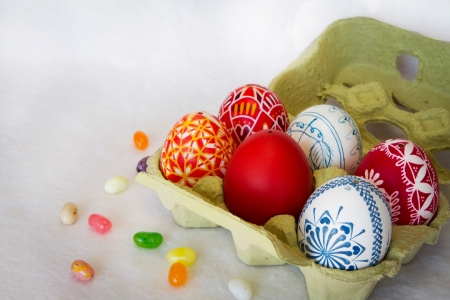 Colorful Easter eggs sit in a carton with jelly beans scattered around  Stock Photo