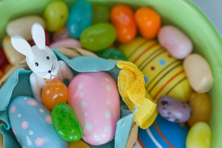 White Easter bunny sits among eggs adn multicolored jelly beans.