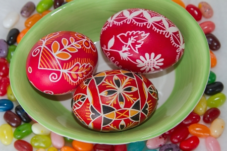 A trio of Easter eggs sit in a green bowl with jelly beans scattered around in a horizontal composition.