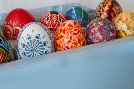 Colorful Easter eggs sit in a blue carton in diagonal composition with copy space.