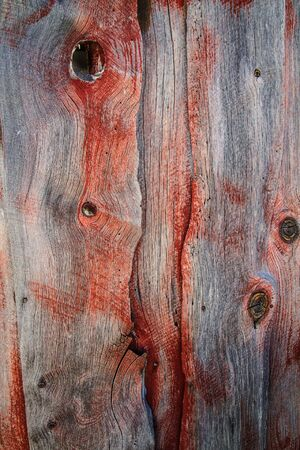 Weathered barn wood shows worn red paint and two eye-like knots in grain. Stock Photo - 17446563