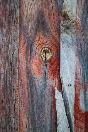 barnwood: Weathered barn wood shows worn red paint and large knot hole with grain. Stock Photo