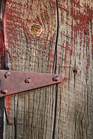 Weathered barn wood shows worn red paint and knots in grain plus  antique hings with bolts.