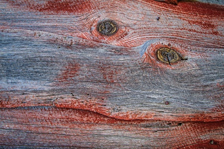 Weathered barn wood shows worn red paint and two eye-like knots in grain. Stock Photo - 17446599