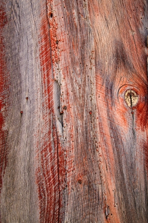 Weathered barn wood shows worn red paint and knots in grain. Stock Photo