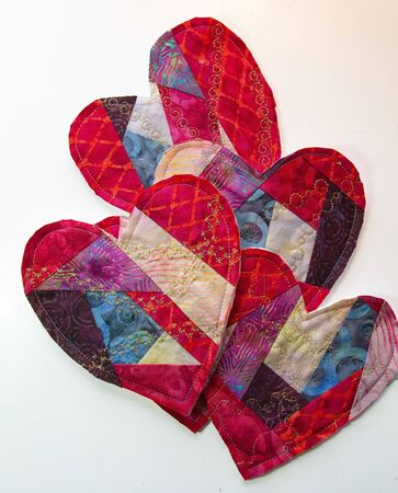 Multiple hand crafted fabric valentines lay overlapping on a white background.