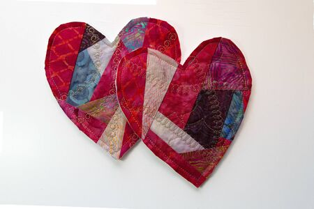 Two hand crafted fabric valentines lay overlapping on a white background. Stock Photo