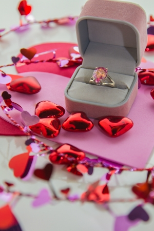 Jeweled ring set in gift box is surrounded by shiny pink and red hearts in a vertical composition.