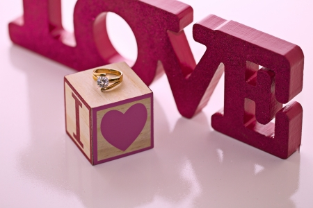 Magenta LOVE block letters with a diamind ring resting on wooden block in a diagonal in a horizontal composition. Stock Photo