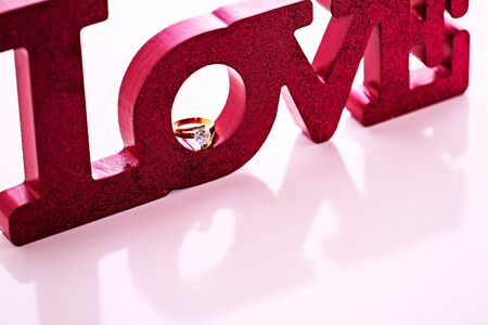 Magenta LOVE block letters with a diamind ring resting in  Stock Photo