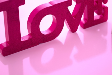 Magenta LOVE block letters reflect at a diagonal in a horizontal composition.
