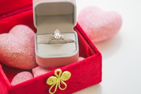 Diamond ring in gift box rests on soft pink hearts inside a red velvet box in horizontal composition.