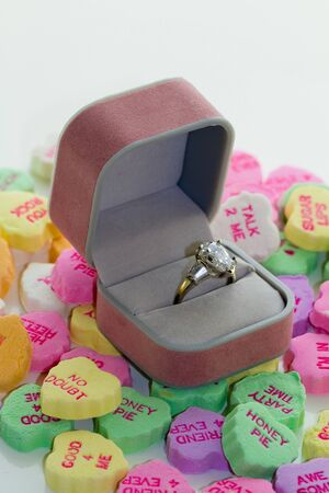 Diamond ring in gift box rests on pastel conversation hearts.