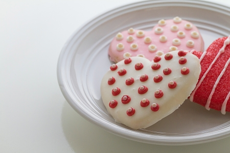 Delicious homemade beautifully decorated valentine cookies rest on plate with horizontal composition and copy space.