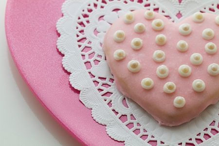 Delicious homemade beautifully decorated valentine cookie rests on pink plate in horizontal composition.