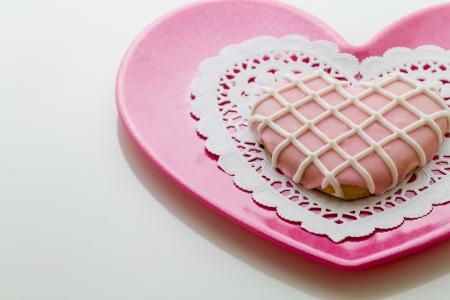 Delicious homemade beautifully decorated valentine cookie rests on pink plate with horizontal composition and copy space.