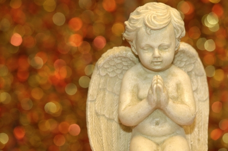 x mass: Praying decoration angel on blurry red background Stock Photo