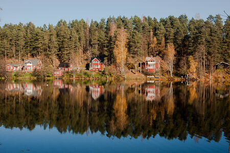 Summer cottages by an autumn lake Stock Photo