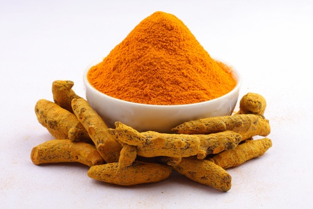 indian spice: Turmeric powder in white bowl with turmeric sticks isolated on white Stock Photo