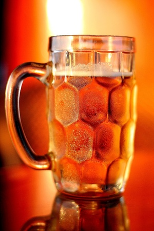 chill out: Mug of chilled beer with forth placed under the yellow colour evening sun light   Stock Photo