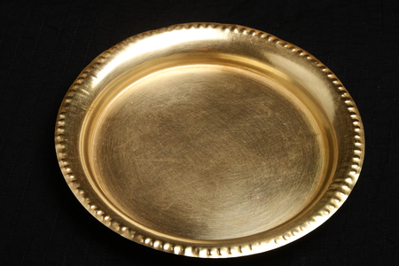 dish disk: Hand made brass plate in black background . Stock Photo