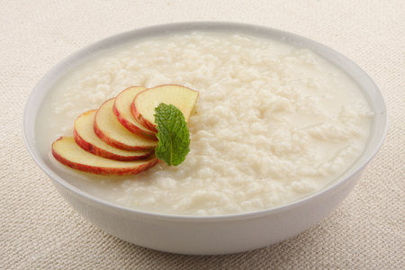 baby rice: Oats  pudding with milk and apples. Stock Photo