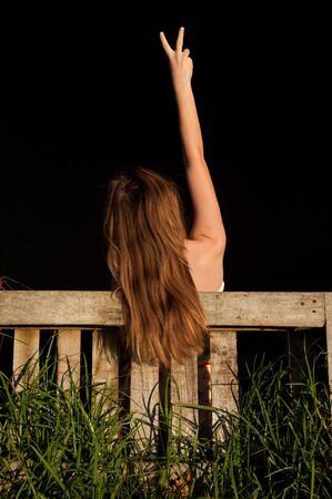 Young teenage girl giving victory sign with hand in the air and long hair falling over farm wooden gate with long grass growing in it. photo