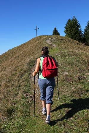 Mountaineering woman walking towards mountain cross, bavarian landscape