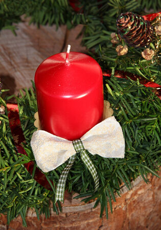 christmas decoration with red candle and jew branches on tree trunk photo
