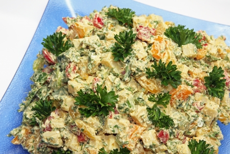 cubed: Cheese salad of cubed emmenthal cheese with parsley and dressing on a glass plate
