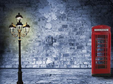 Paesaggio Vintage, muro di mattoni, lanterna e cabina telefonica, scenario serale in strada Archivio Fotografico - 24979963