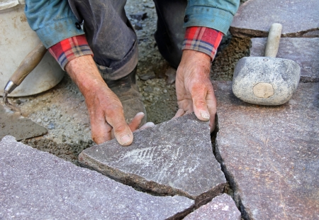 シニア庭師舗装自然石のテラス、プロの精密な作業の手 写真素材