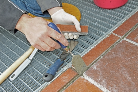 worker repairing and grouting patio outdoors