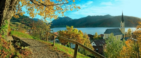 foothills: beautiful panoramic view to schliersee village in autumn, lookout point with bench and lime tree in october Stock Photo