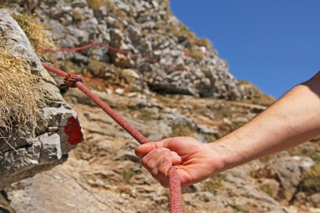 Hand of mountain climber, holding on a climbing rope photo