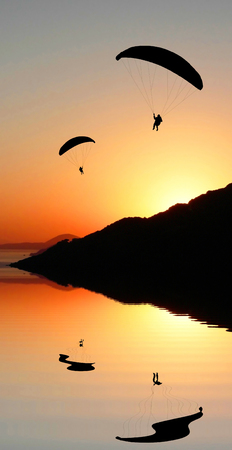 peace risk:  Two silhouette paragliders flying in the sunset sky, coastal landscape with water reflection, romantic mood