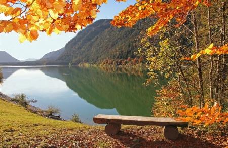 Panorama-Blick auf Sylvensteinsee, Holzbank an einem Aussichtspunkt, schöne herbstliche Landschaft Bayerns