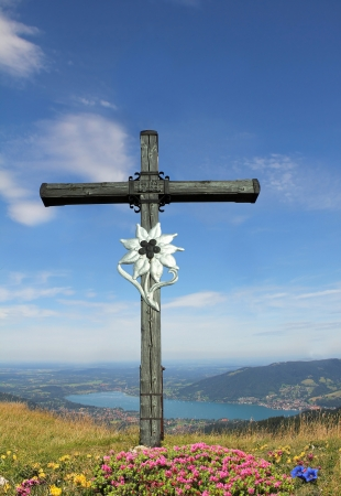 Wooden mountain cross with edelweiss and alpine flowers, view to bavarian lake tegernsee , german landscape photo