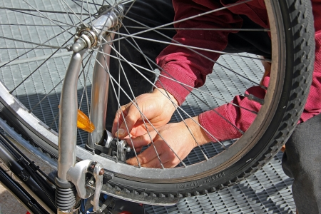 Closeup of a man, doing bicycle repairs and maintenance, at home photo