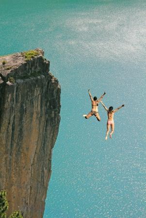 クリフ ジャンプの 2 つの女の子は、ターコイズ ブルーの海、フォト モンタージュに対して 写真素材