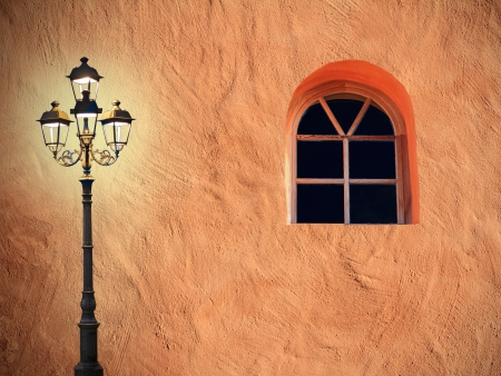 lattice window: Mediterranean house facade with glooming lantern and arched lattice window Stock Photo