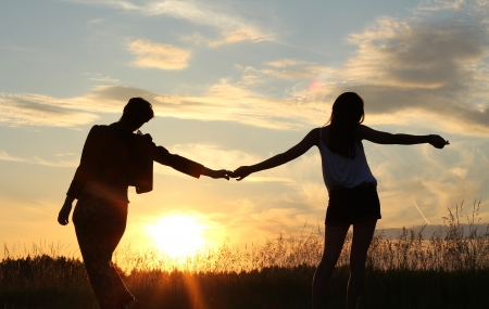teenage sisters, holding hands - sunset silhouette