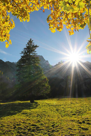 bright sunburst, autumnal landscape karwendel, golden october in austria photo