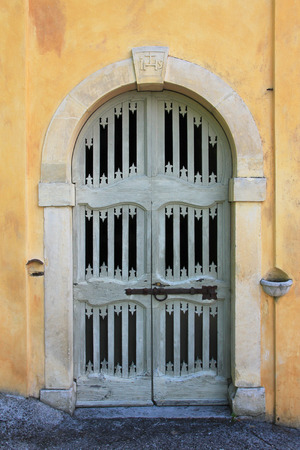 Old wooden arched chapel door and yellow wall  Stock Photo