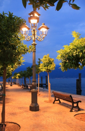 Burning lantern at the lakeside Promenade of garda lake, romantic mood