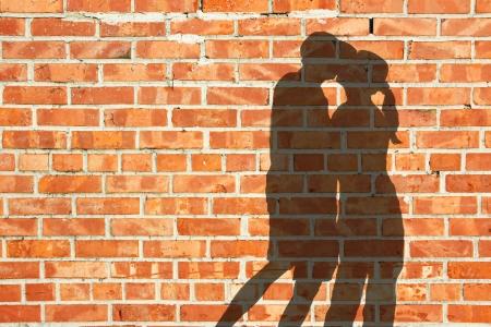붉은 벽돌 벽에 키스 실루엣 부부 스톡 콘텐츠