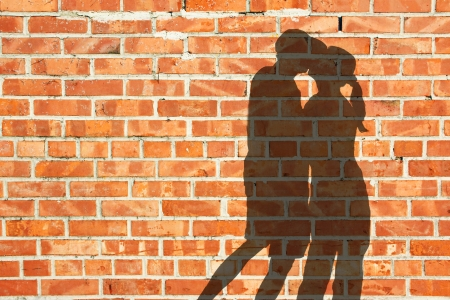 Kissing silhouette couple against red brick wall  Stockfoto