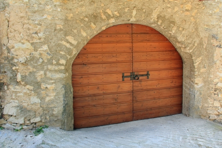 view of a wooden doorway: Wooden arched garage door