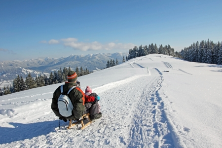 father and son on the sleigh, bavarian mountains