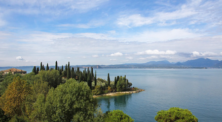 picturesque mediterranean lakeside of garda lake with cypresses, italy
